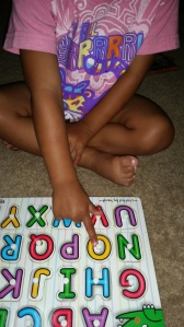 Picking out O in the alphabet puzzle.