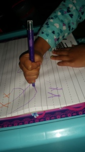 Trying to write X on her own, like mommy!