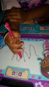 Trying to write the letter Y on her own
