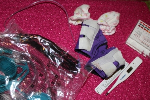 Her daily items.  Feeding bag, hand splints, thermometer, mittens, PH test strip, feeding tube