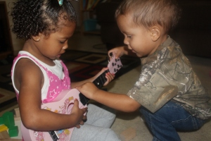 Brielle teaching Aiden how to play her guitar