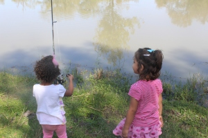 Brielle teaching Emma how to fish