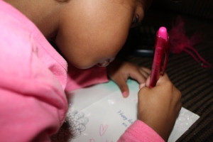 Brielle writing in her sisters birthday card.
